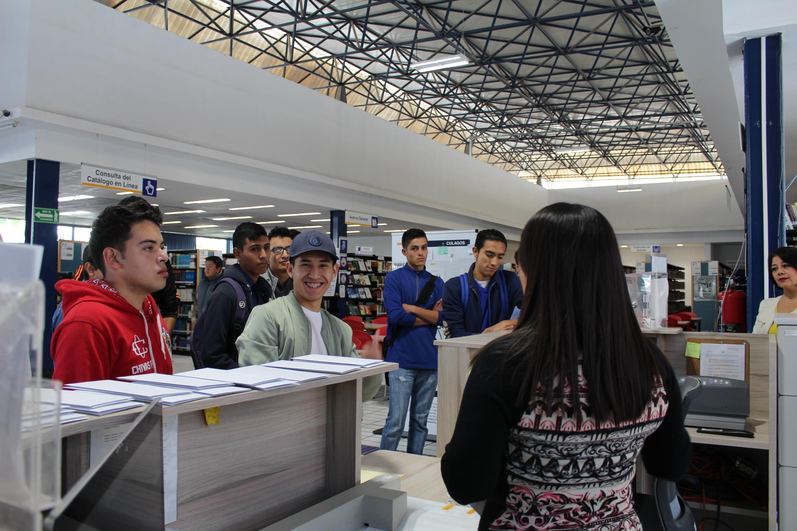 Estudiantes de nuevo ingreso en la biblioteca, recibiendo instrucciones sobre su reto