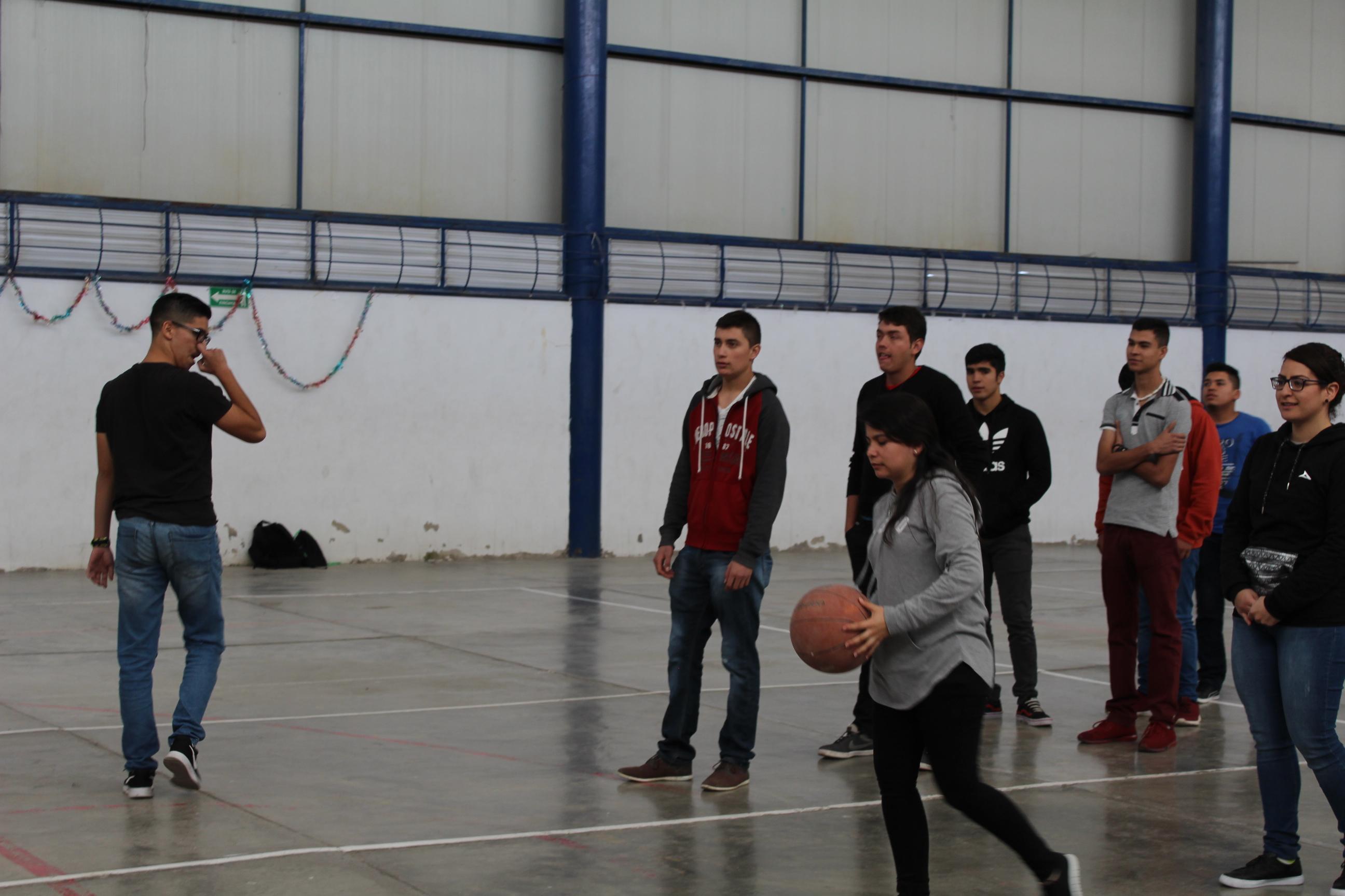 Estudiantes practicando el encestando del balón de básquetbol