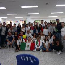 Estudiantes de intercambio en Colombia, al centro Óscar y una compañera suya sostienen la bandera de México