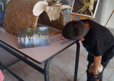 """Niño escribiendo en la libreta de la exposición """"Nuestras raíces"""""""